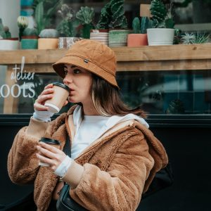 woman in brown coat holding white ceramic mug